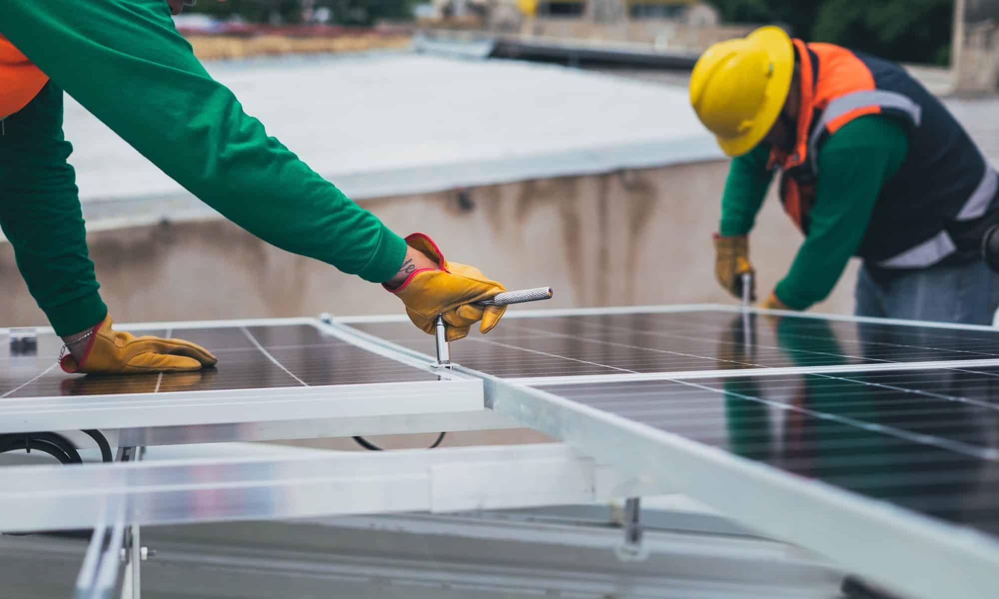 Työntekijät asentavat aurinkopaneeleja