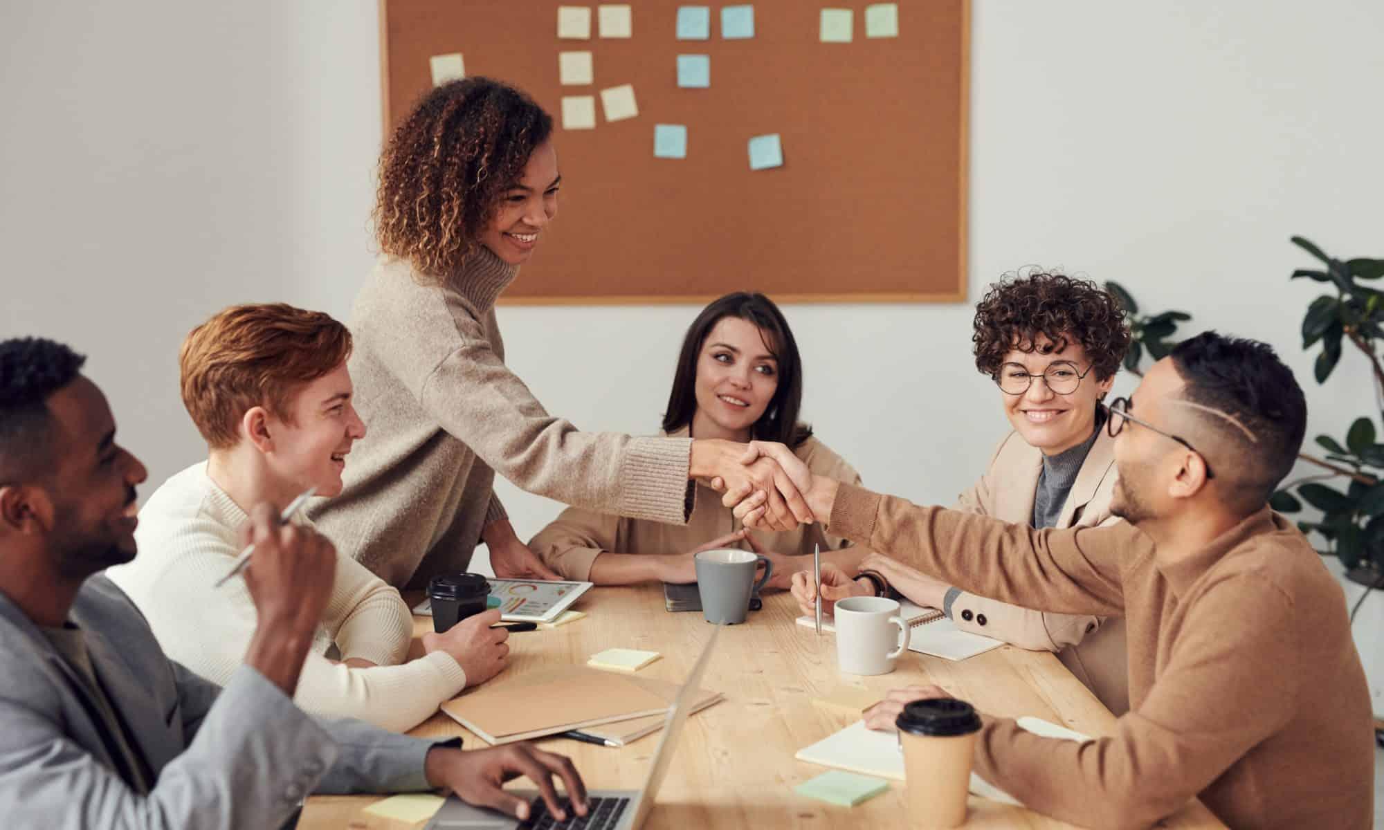 Ludzie w pracy spotykają się i ściskają ręce