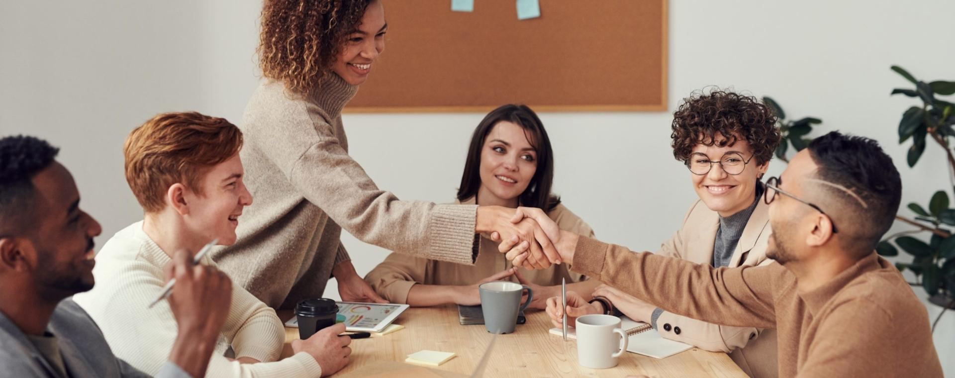 Ludzie w pracy spotykają się i podają sobie ręce