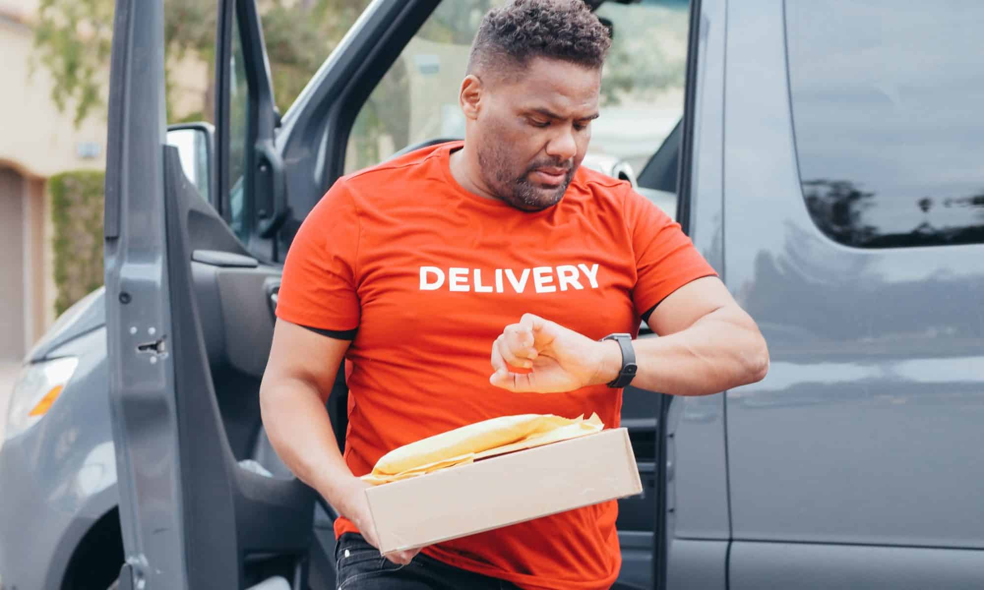 Delivery man steps out of truck and checks watch